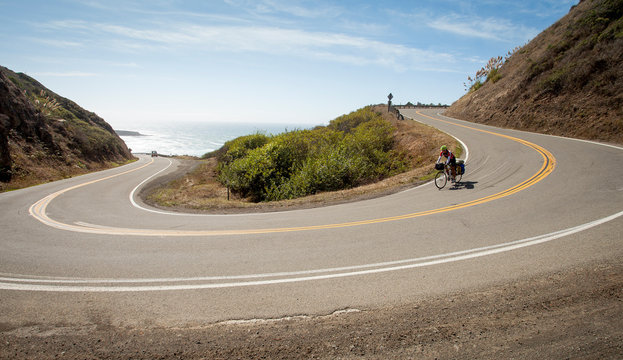 Women descending hairpin turn on the California Coast Highway on Cross country bike with panniers.
