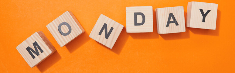 panoramic shot of wooden cubes with letters on orange surface
