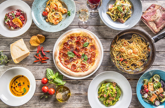 Top of view full table of italian meals on plates and pan. Pizza pasta risotto soup and fish vegetable salad