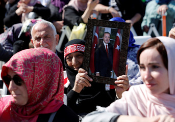 A woman holds a picture of Turkish President Erdogan during the opening ceremony of Grand Camlica Mosque in Istanbul