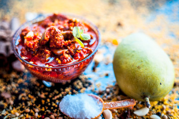 Obraz Popular Indian & Asian pickle of mango in a glass bowl i.e. Aam ka achar in a glass bowl or keri ka achar with its entire raw ingredients including spices and mango on black colored shiny surface. - fototapety do salonu