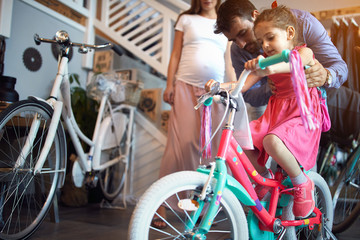 Young family buying new bicycle for little girl in bike shop . Fototapete