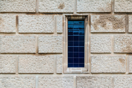 A window on the stone facade of the historic building front view closeup, Barcelona, Catalonia, Spain