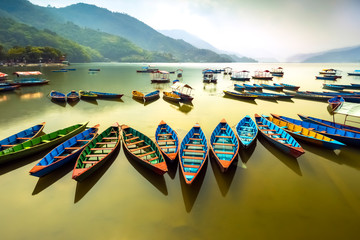 Amazing view on Phewa Lake. colorful boats at queued at a midday. Wall mural