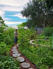 Permaculture Backyard with Natural Pool looking to Man Working on Plants