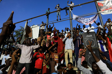 Sudanese protesters shout slogans and make victory signs during a demonstration in front of the defense ministry compound in Khartoum