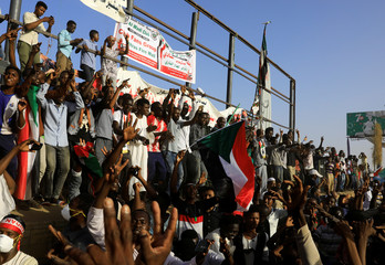 Sudanese protesters shout slogans, make victory signs and wave national flags during a demonstration in front of the defense ministry compound in Khartoum