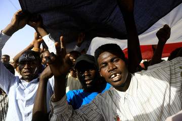 Sudanese protesters make victory signs during a demonstration in front of the defense ministry compound in Khartoum