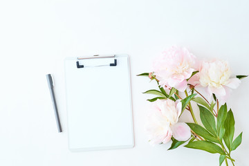 Flat lay blogger or freelancer workspace with a clipboard,  light pink peonies on a white background