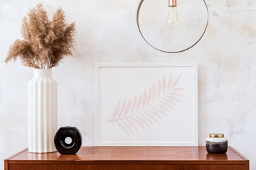 Stylish and elegant home interior of living room with design retro cabinet, mock up photo frame, round pendant lamp, palm leaves and elegant accessories. Minimalistic home decor. Real photo.