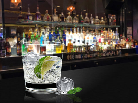 A glass of gin tonic or vodka lime with ice on bar counter and blurry bottles background