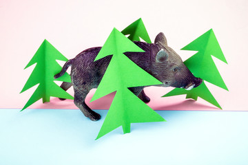 toy figure of a wild boar walking in the forest, picture on a pink-blue background, concept of hunting in the reserve
