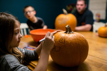 Young girl drawing a face on a pumpkin at table with family