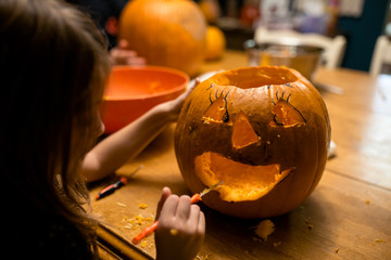 Young girl carving a pumpkin at table with family