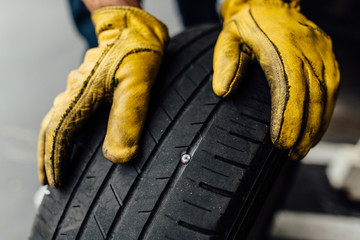 Dirty yellow leather mechanic gloves holding car tire with nail in it