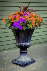Old pedestal style planter with purple petunias and orange impatiens.