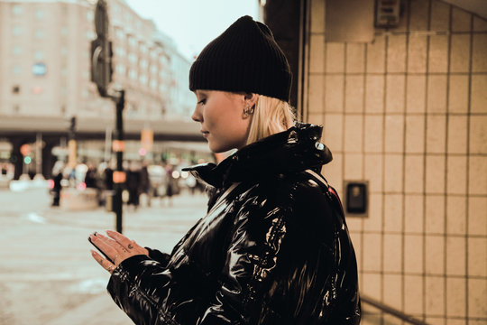 Side view of young woman using mobile phone while wearing black shiny jacket at subway's entrance in city during winter