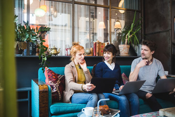 Smiling colleagues looking at female manager sitting with laptop on sofa at creative office