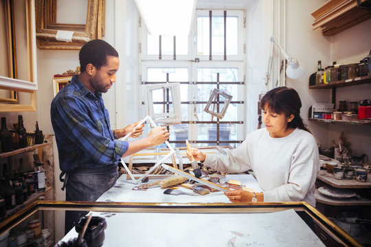 Male and female artists making picture frame at workbench in store