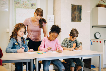 Teacher looking at students writing at desk in elementary classroom