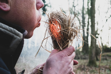 Close up of man blowing on bundle of straw, igniting fire.