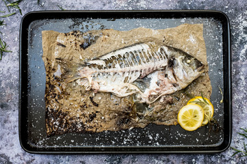 High angle close up of skeleton of grilled sea bream on baking tray.