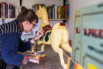 Woman standing in workshop, painting a traditional wooden carousel horse from merry-go-round.,Signwriter