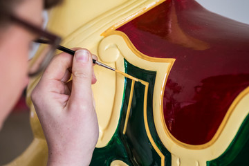 Close up of woman wearing glasses in a workshop, painting traditional wooden horse from merry-go-round.,Signwriter