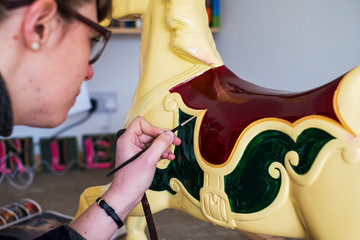 Close up of woman in workshop, painting traditional wooden carousel horse from merry-go-round.,Signwriter