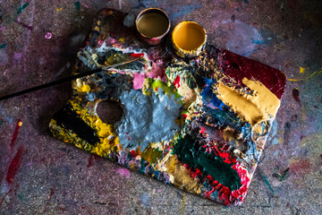 High angle close up of painter's palette, oil paints and paintbrush in a workshop.,Signwriter