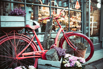 Poster de jardin Velo Summer landscape with a bike in the style of Provence. Urban bike parked to a flower shop. Bicycle with a basket for flowers stands near a beautiful place.