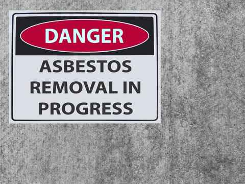 the sticker Sign danger asbestos removal on the plaster asbestos wall