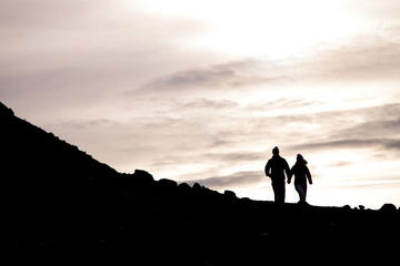 Silhouette of couple holding hands while walking on mountain at sunset
