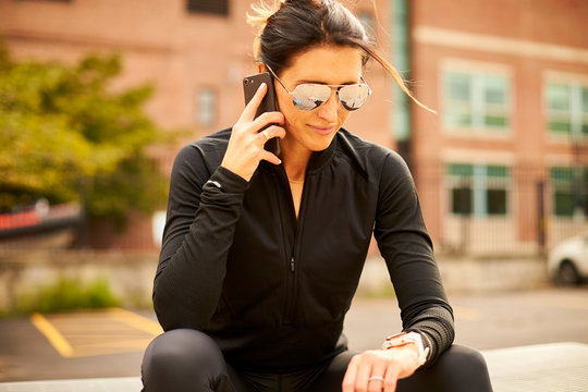 A woman looks at her fitness watch while talking on her smartphone.