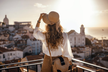 Blonde woman standing on the balcony and looking at coast view of the southern european city with sea during the sunset, wearing hat, cork bag, safari shorts and white shirt Wall mural