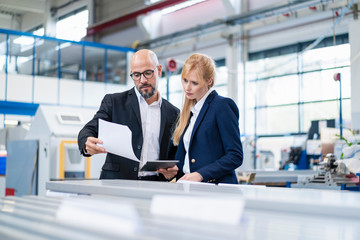 Businessman and businesswoman looking at paper in factory