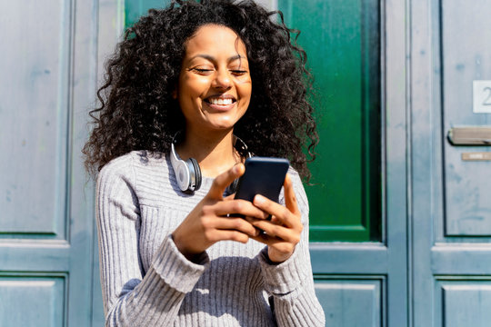 Laughing woman holding smartphone