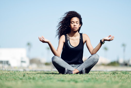 Sporty young woman doing yoga on lawn