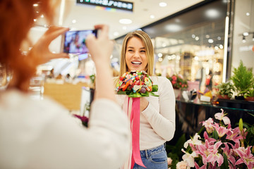 Happy woman holding candy bouquet in a shop posing for a photo