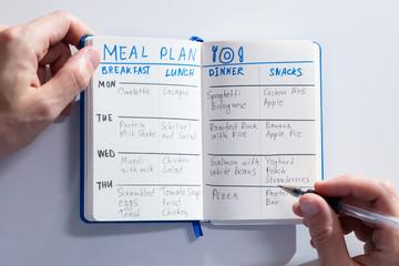 Filling Meal Plan In Notebook At Desk