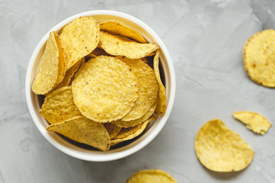 Tortilla corn chips in bowl an a gray background