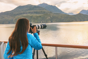 Wall Mural - Travel photographer with professional telephoto lens camera on tripod shooting wildlife in Alaska, USA. Scenic cruising inside passage cruise tourist vacation adventure. Woman taking photo picture.