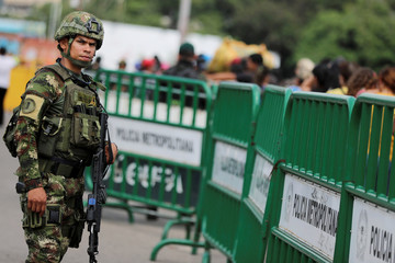 A Colombian army member observes the passage of people on the Simon Bolivar international bridge, after a shooting near to the border between Colombia and Venezuela, in Cucuta