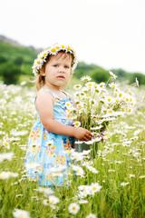 toddler girl in a daisy field