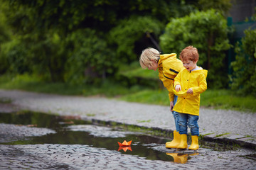 happy young boys, friends playing in spring puddles with colorful paper boats
