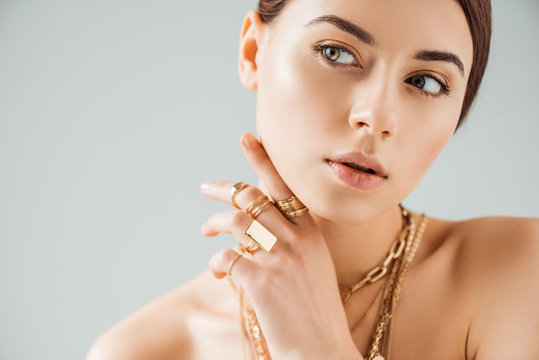 young nude woman in golden rings and necklaces looking away isolated on grey