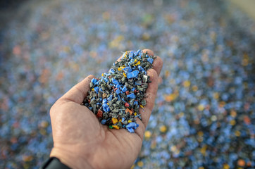Fototapeta Hand holding recycled plastic chips as raw material in production. obraz