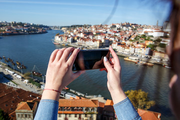 A girl is photographing a panorama of Porto city, Portugal.