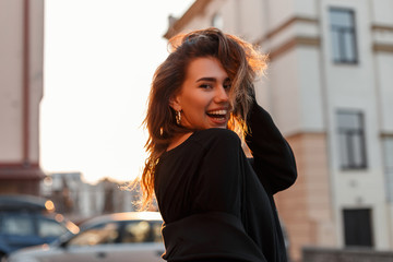 Funny positive young woman in stylish black clothes posing and smiling positively in the city on a background a spring bright orange sunset. Attractive joyful girl travels and enjoys the sunshine. Fotomurales