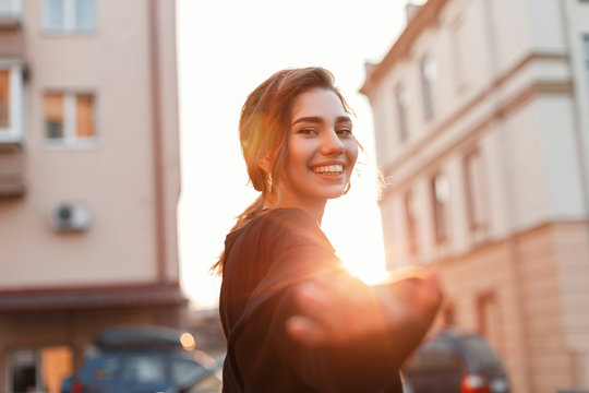 Portrait of a cheerful joyful beautiful young woman with a cute smile in fashionable black clothes outdoors in the city on a bright sunny day. Positive funny girl model enjoys an orange sunset. Enjoy.